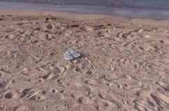 Chancletas en la arena sin el dueño imágenes de archivo libres de regalías