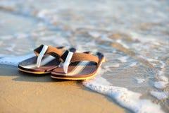 Chancletas en una playa arenosa del océano Fotografía de archivo libre de regalías