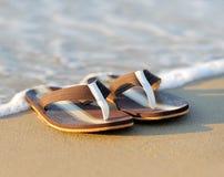 Chancletas en una playa arenosa del océano Fotos de archivo libres de regalías