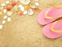 Chancletas rosadas con las cáscaras del mar en la arena de la playa Fotografía de archivo