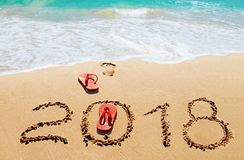 Chancletas y dígitos rojos 2018 en la playa Fotografía de archivo libre de regalías