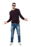 Chandail de port et lunettes de soleil de jeune homme incertain gesticulant des épaules Photographie stock