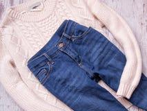 Chandail et jeans blancs sur un fond en bois Concept à la mode, vue supérieure Photographie stock libre de droits