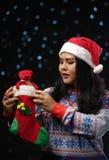Chandail et Santa Hat Holding Chris de port de Noël de fille asiatique photographie stock libre de droits