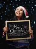 Chandail et Santa Hat Holding Merry de port de Noël de fille asiatique photo stock