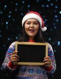 Chandail et Santa Hat Holding Small de port de Noël de fille asiatique image stock
