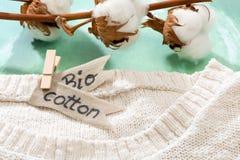Chandail fait en tissus naturels et branche avec des fleurs de coton photos libres de droits