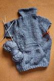 Chandail gris de tricotage inachevé pour l'enfant avec des aiguilles photo libre de droits