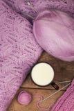 Chandail lilas avec une tasse de lait sur une table en bois Photo stock