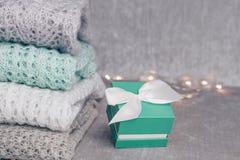 Chandails colorés en pastel tricotés élégants pliés dans la pile avec la boîte actuelle colorée par menthe avec l'arc blanc de sa photographie stock libre de droits