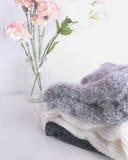 Chandails de blanc gris et de noir sur un bureau blanc Fleurs roses décoratives dans un pot Habillement automnal et hivernal Images stock