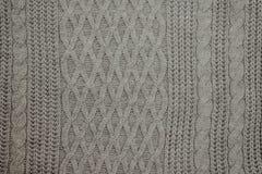 Chandails de laine tricotés pliés, pile de vieux livres sur une couverture beige pelucheuse confortable images stock