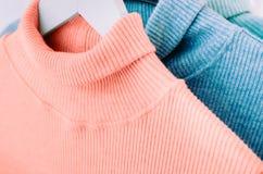 Chandails sur la couleur de corail bleue et à la mode de cintre photographie stock libre de droits