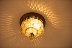 Chandelier. A beautiful ornate lit chandelier reflecting against the ceiling royalty free stock images
