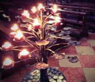 Chandelier avec beaucoup de bougies allumées par le fidèle à l'intérieur d'un churc image libre de droits