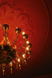 Chandelier on ceiling. Classic chandelier on the red ceiling Royalty Free Stock Images