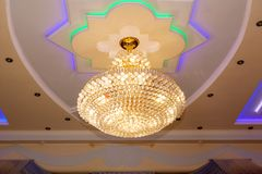 Chandelier on the ceiling. Round rich chandelier with a design on the ceiling with space for text stock image