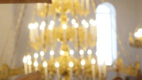 Chandelier in the church. Candles are lit on the chandelier in the orthodox church. In the background, a large. Iconostasis stock footage