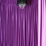 Chandelier and curtains. Black chandelier against a background of beautiful heavy colored curtains royalty free stock images