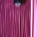 Chandelier and curtains. Black chandelier against a background of beautiful heavy colored curtains stock image
