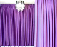 Chandelier and curtains. Black chandelier against a background of beautiful heavy colored curtains stock photos