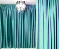 Chandelier and curtains. Black chandelier against a background of beautiful heavy colored curtains stock photo