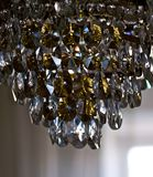 Chandelier in a dark room. Crystal chandelier, in a dark room, as if illuminated from the inside. Her cut-glass pendants catch the subtle rays of light and Royalty Free Stock Image