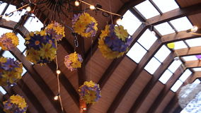Chandelier is richly decorated with garlands made from artificial flowers. stock footage