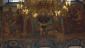 The chandeliers and the frescoes in the Church. Gorgeous and ancient iconostasis in the Cathedral of St. Petersburg.  stock video