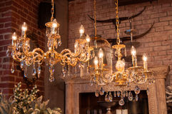 Chandeliers. Glittering chrystal chandeliers hanging on the ceiling of an art and furniture shop Stock Image