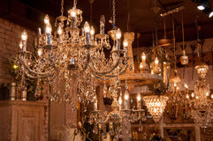 Chandeliers. Glittering chrystal chandeliers hanging on the ceiling of an art and furniture shop Stock Photos
