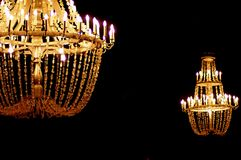 Chandeliers hanging in the gloom. Chandeliers whose light scarcely pierces the darkness, seeming to float in the air stock images