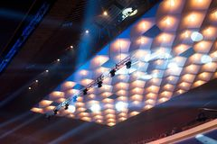 Chandeliers and stage lights under the ceiling. Of the concert hall stock photos