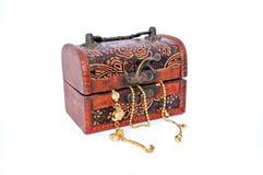 Chaînes d'or dans une boîte en bois découpée fermée de trésor Images stock