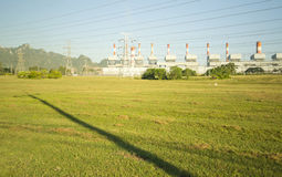 Changchai. Shadow of Electricity post on green field with coal-fired power plant in background Stock Images