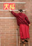 Change. A monk changes signs at a buddhist temple royalty free stock image