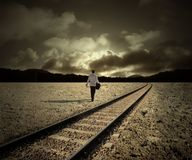 Change. Man walking along train tracks