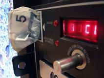 Change. A $5 bill being inserted into a coin slot in a generic pop machine Stock Photos