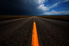 Change Ahead. A straight road leading into changing weather Royalty Free Stock Photo