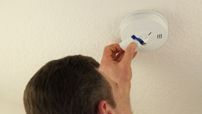 Change Battery Smoke Detector. Man changing a modern ceiling smoke alarm detector battery so the fire alarm device will warn people in the home of danger so they stock video