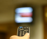 Change the Channel. Hand using a remote control. TV blurred in the background Stock Photo
