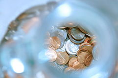 Change is here. Change in a jar. Blurred Glass bottle containing change stock photography