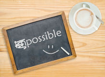 Change impossible to possible on chalkboard. With coffee cup Stock Image