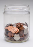 Change jar. A jar of loose US coins stock photography