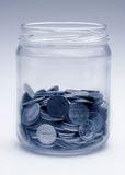 Change jar in monochrome blue. A jar of loose US coins, monochrome with a blue tint royalty free stock image