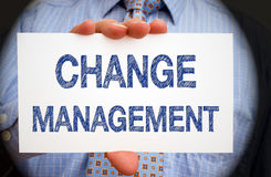Change Management - Manager holding sign with text. Change Management - Manager holding white sign with blue text in his hand, spotlight effect stock images