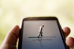 Change for New Challenge in Life or Upgrade Technology Concept. Miniature Fugure of Businessman Walking with Update Progressive Bar on Smartphone Screen stock photography
