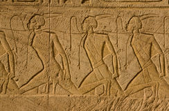 Change of nubian slaves. Bas-relief which shows the Nubian slaves under the lash of the pharaoh Royalty Free Stock Photo