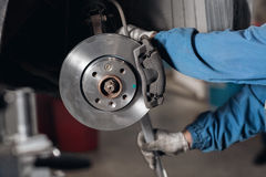 Change the old drive to the Brand new brake disc on car in a garage. Auto mechanic repairing . Stock Image