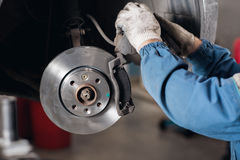 Change the old drive to the Brand new brake disc on car in a garage. Auto mechanic repairing . Stock Images